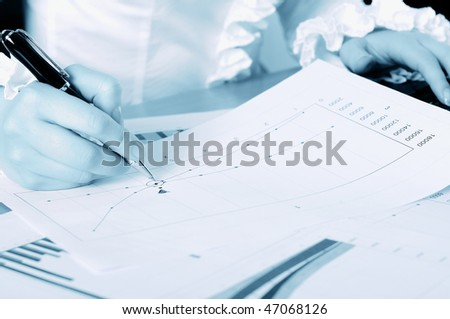 hand of a young business woman working with documents. Workplace of business people.