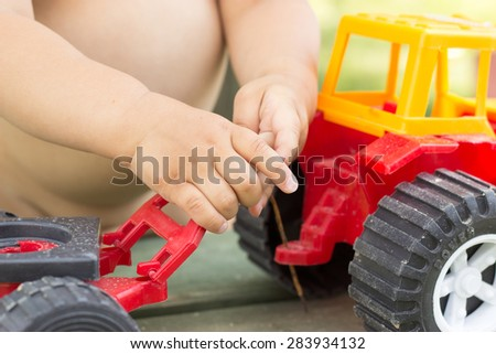 hand of a young child holding a toy red tractor - stock photo