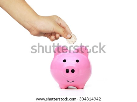 hand of a young female child putting a coin into a pink piggy bank - kid saving money for future concept - stock photo