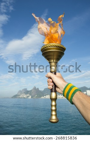 Hand of an athlete wearing Brazil colors sweatband holding Olympic sport torch against Rio de Janeiro Brazil skyline with Two Brothers Mountain - stock photo