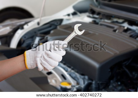Hand of auto mechanic with wrench, car repair service centre - stock photo