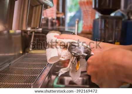 Hand of barista cleaning coffee machine at coffee shop.