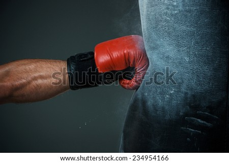 Hand  of boxer and punching bag over black background - stock photo