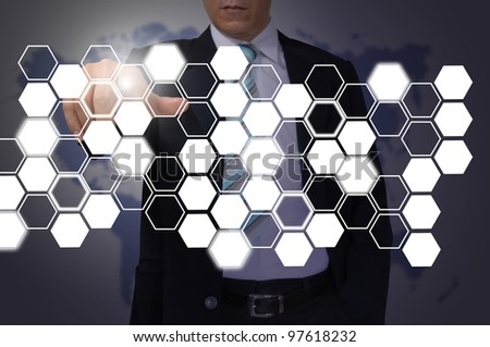Hand of Business Man Pressing or Pushing hexagon button on touch screen interface - stock photo