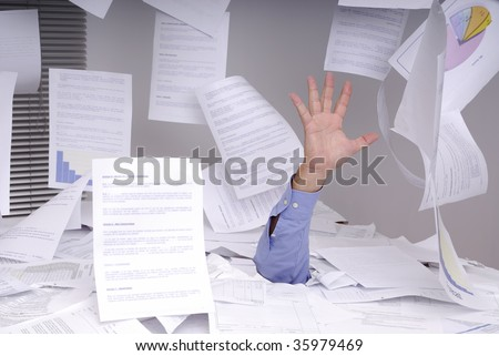 Hand of business man sticking out of a desk full of papers and flying papers