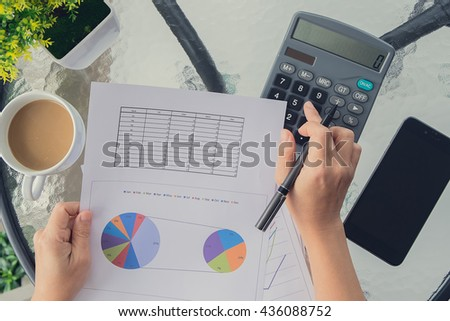 Hand of business woman working with documents and calculator on the desk  - stock photo