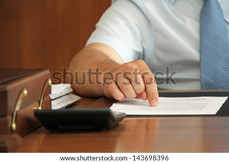 Hand of businessman at desk with document point finger on paper. Shallow depth of field. - stock photo