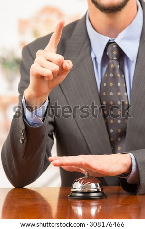 hand of businessman customer ringing hotel bell in reception desk demanding attention close up - stock photo