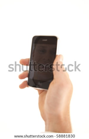 Hand of businessman holding cell phone with refection of face - stock photo