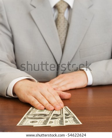 Hand of businessman holding dollars on table - stock photo