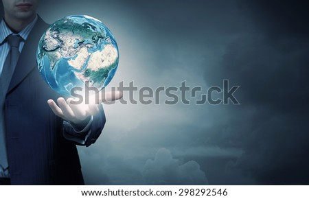 Hand of businessman holding earth planet. Elements of this image are furnished by NASA - stock photo