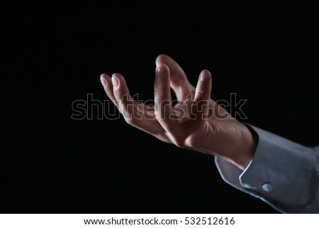 Hand of businessman on black background