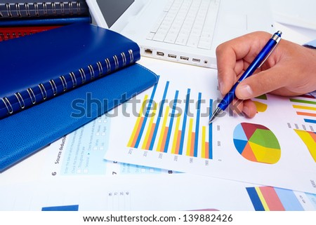 Hand of businessman with a pen. Finance and accounting business background.