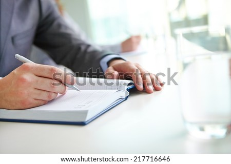 Hand of businessman with pen writing in notebook at seminar - stock photo