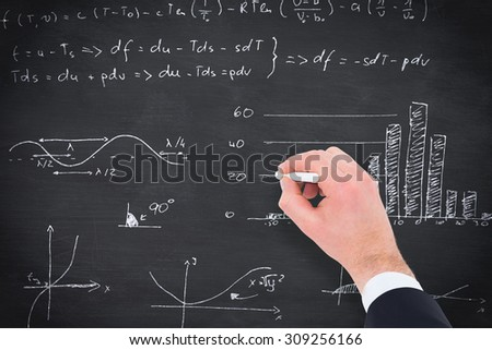 Hand of businessman writing with a white chalk against blackboard - stock photo