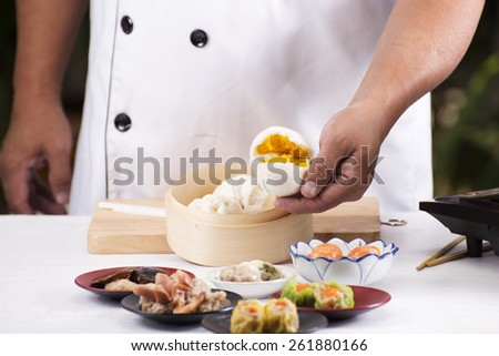 Hand of chef holding steamed dumpling bun / Cooking Dim sum concept
