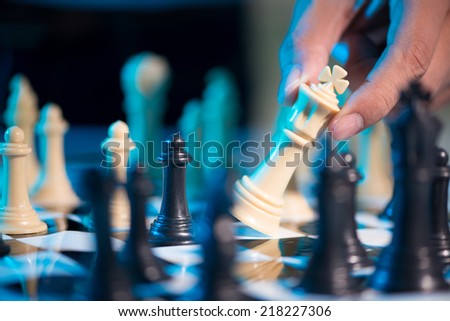 Hand of chess player moving the king - stock photo