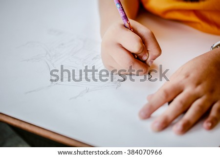 Hand of children drawing with pencil - stock photo