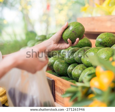 Hand of customer choosing avocados at the supermarket, selective focus - stock photo