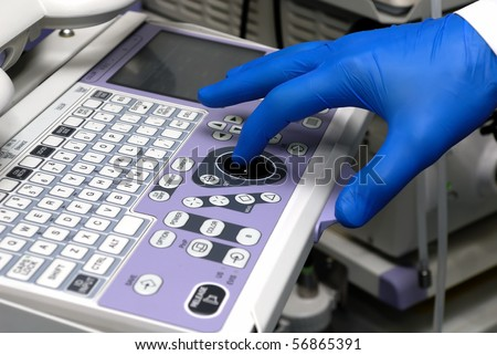 Hand of doctor managing medical equipment - stock photo
