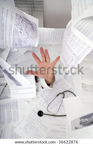 hand of doctor sticking out of a desk full of papers - stock photo