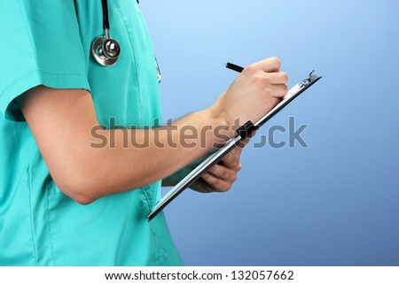 Hand of doctor with pen writing on prescription blank, on blue background - stock photo
