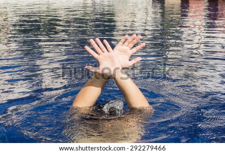 Hand of drowning man in a swimming pool - stock photo