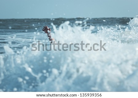 Hand of drowning man trying to swim out of the stormy ocean. - stock photo