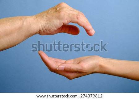 Hand of elderly woman above young woman's hand on blue background