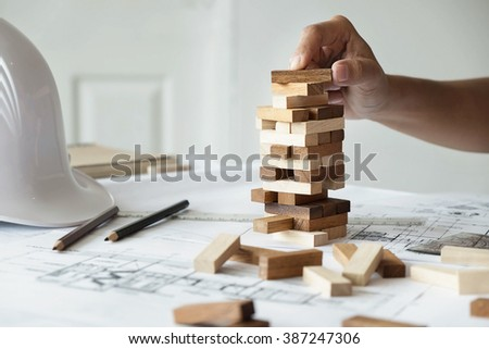 Hand of engineer playing a blocks wood game (jenga) on blueprint or architectural project. - stock photo