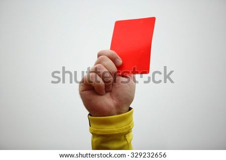 Hand of football referee holding up red card - stock photo