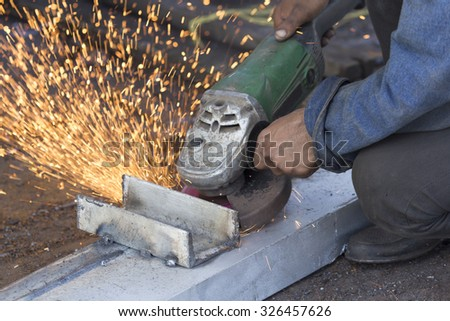 Hand of grinding worker during hot summer - stock photo