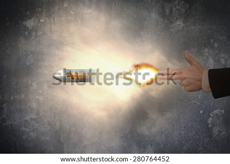 Hand of gun gesture with firelight shooting the dollar sign bullet - stock photo