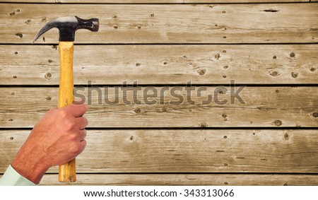 Hand of handyman with a hammer. House renovation and construction.