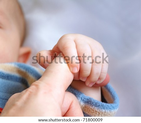 Hand of kid which holds on to the finger of parent