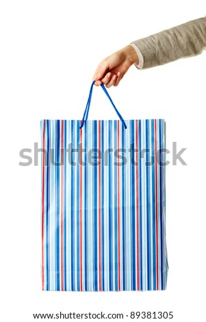 Hand of lady carrying blue paper bag - stock photo