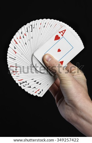 Hand of magician with cards on black background - stock photo