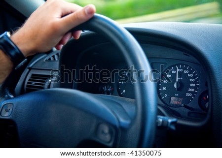 Hand of man driving a car - stock photo
