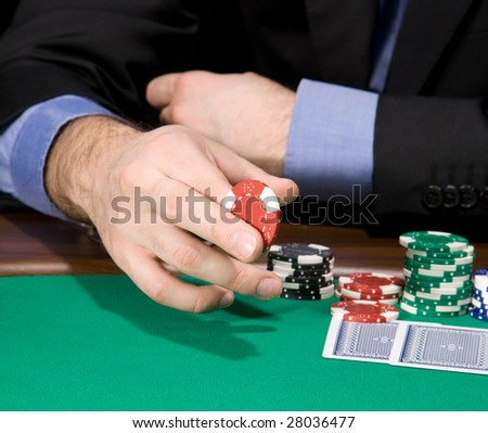 Hand of man holding casino chip over green felt