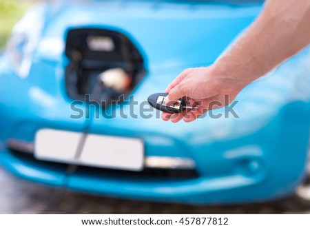 Hand of man holding key for car