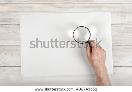 Hand of man holding the magnifying glass over white paper lying on wooden surface - stock photo