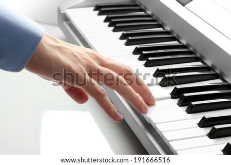 hand of man playing piano - stock photo