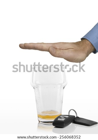 Hand of man refusing any more beer in his empty glass next to car keys on a white background - stock photo