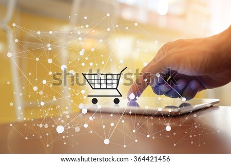 Hand of man shopping by cart from taplet. Concept of buying digital online.