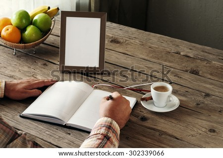 Hand of man writing in a blank notebook on the wooden table. Next on the table is an empty frame. Top view. Copy space. Free space for text - stock photo