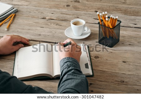 Hand of man writing something in blank notebook on wooden table. Closeup. View from above. Copy space. Free space for text - stock photo