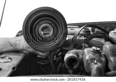 Hand of mechanic holding an engine pulley, isolated on white shot