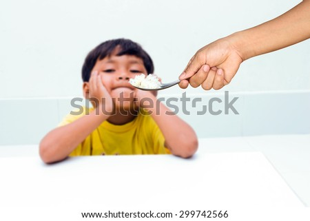Hand of mother give food for children, who are tired of rice. focus at rice. - stock photo