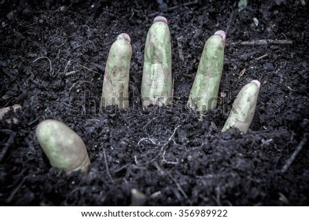 hand of murdered woman buried under the ground - stock photo