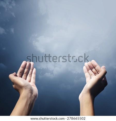 Hand of muslim people with praying gesture praying facing sky - stock photo